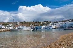 米科诺斯岛,希腊- 2010年5月04日:与小船的海海滩在多云蓝天 山风景的议院由海 免版税库存图片