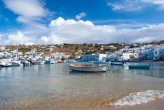米科诺斯岛,希腊- 2010年5月04日:在海水的小船 在多云蓝天的海海滩 山风景的议院与 免版税图库摄影