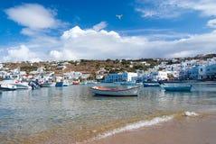 米科诺斯岛,希腊- 2010年5月04日:在海海滩的小船 在多云蓝天的沿海 有房子的地中海村庄 免版税库存照片