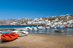 米科诺斯岛,希腊- 2010年5月04日:在海海滩的小船 有白色房子的村庄山风景的蓝色海的 夏天 图库摄影