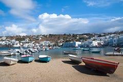 米科诺斯岛,希腊- 2010年5月04日:在海海滩的渔船 有白色房子的村庄山风景的蓝色海的 免版税库存照片