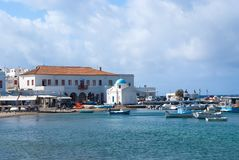 米科诺斯岛,希腊- 2010年5月04日:在海海滩的渔船 村庄在多云天空的海边 教会和房子海上 免版税图库摄影