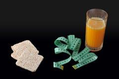 米薄脆饼干、一杯橙汁和测量的磁带 图库摄影