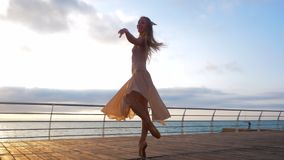 米黄丝绸礼服的跳舞在堤防的芭蕾舞女演员和pointe在日出的海洋上 年轻美丽的白肤金发的妇女与 股票视频