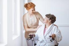 米黄制服的护士用她的在资深妇女肩膀的手 免版税库存照片