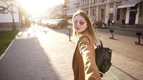 米黄外套步行的白肤金发的长发女孩穿过充分城市阳光 E 妇女和 股票视频
