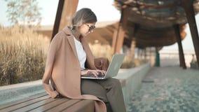 米黄外套的镇静白肤金发的妇女与膝上型计算机一起使用在公园 股票录像