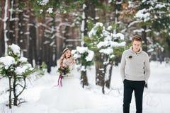 米黄套头衫的英俊的新郎在被弄脏的新娘背景多雪的森林冬天婚礼的 附庸风雅 库存图片