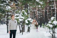 米黄套头衫的英俊的新郎在被弄脏的新娘背景多雪的森林冬天婚礼的 附庸风雅 免版税库存照片