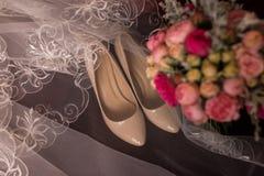 米黄新娘说谎在一把红色扶手椅子的鞋子和面纱 与桃红色玫瑰的婚礼花束在焦点外面 免版税库存图片