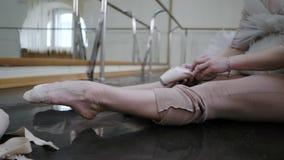 米黄服装揉的腿的年轻芭蕾舞女演员在投入在芭蕾舞鞋pointe前 妇女为舞蹈训练做准备 影视素材