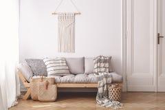 米黄木沙发和袋子在白色顶楼内部与装饰在墙壁上在门旁边 实际照片 免版税库存照片