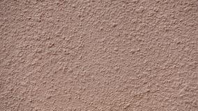米黄涂灰泥的墙壁纹理背景的 库存图片