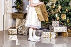 米黄礼服的一个女孩装饰与玻璃圣诞节球和玩具的圣诞树 图库摄影