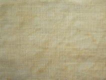 米黄自然纺织品织地不很细背景  免版税库存照片