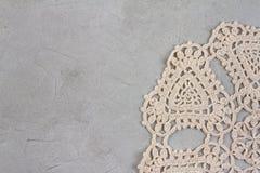 米黄螺纹美丽的老餐巾刺绣手工制造在具体概略的背景 免版税图库摄影