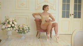 米黄衣物、米黄bodyfoot和米黄pointes的一位年轻美丽的芭蕾舞女演员下在减速火箭附近坐或站立 股票录像