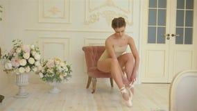 米黄衣物、米黄bodyfoot和米黄pointes的一位年轻美丽的芭蕾舞女演员下在减速火箭附近坐或站立 股票视频