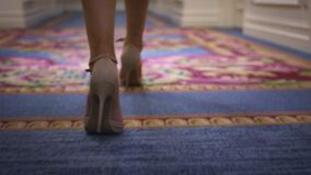 米黄鞋子的性感的妇女走在地毯地板后面视图的 股票录像