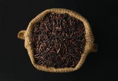 米, riceberry在黑背景的大麻大袋 库存照片