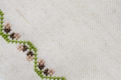 米黄亚麻制织品纹理与刺绣的 免版税库存照片