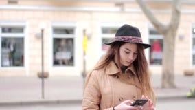 米黄外套黑色浅顶软呢帽帽子的悦目女孩使用在街道上的智能手机 股票录像