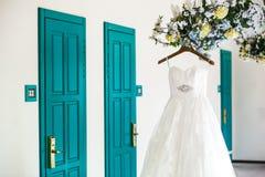 米黄婚礼礼服在枝形吊灯的钉垂悬 库存照片