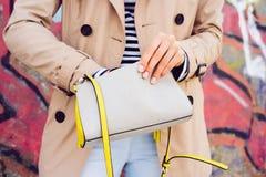 米黄拿着在后面的外套和牛仔裤的妇女夫人的提包 库存图片