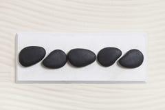 黑米黄背景的五块黑石头 免版税库存图片
