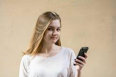 米黄背景的美丽的逗人喜爱的女孩 没有任何人 有嫉妒的白肤金发的女孩 她看照相机并且微笑 Busines 库存照片