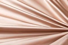 米黄背景豪华布料或难看的东西丝绸纹理缎天鹅绒波浪折叠  免版税库存照片