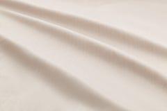 米黄背景豪华布料或难看的东西丝绸纹理缎天鹅绒波浪折叠  库存照片