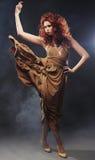 米黄长的礼服的少妇 免版税库存照片