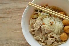 米细面条顶部虾球和切片煮沸的猪肉在汤由木筷子吃 库存照片
