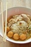 米细面条顶部虾球和切片煮沸的猪肉在汤由木筷子吃 库存图片