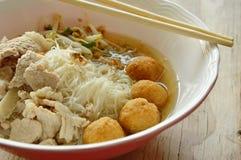 米细面条顶部虾球和切片煮沸的猪肉在汤由木筷子吃 免版税库存图片