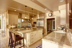 米黄颜色的大豪华厨房室与花岗岩桌面和砖地 免版税库存照片