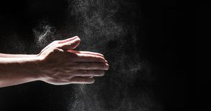 粉状面粉飞行到作为人的空气里黑厨师成套装备的擦去他的手 免版税库存照片