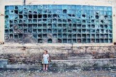 粉碎的墙壁 残破的玻璃,小无防御的女孩 免版税图库摄影