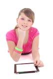 粉红色的位于的十几岁的女孩与片剂个人计算机 库存照片
