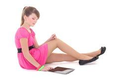 粉红色的坐的十几岁的女孩与片剂个人计算机 免版税库存图片