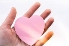 粉色心形的纸在手中在白色背景 库存图片
