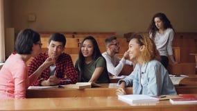 粗心大意的女孩和男孩谈话,并且笑的坐在书桌在教室,学生在断裂期间是松弛 股票视频