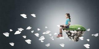 粗心大意的愉快的童年的概念与女孩阅读书的 免版税库存图片
