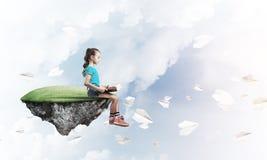 粗心大意的愉快的童年的概念与女孩阅读书的 免版税图库摄影