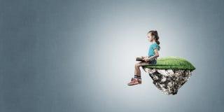 粗心大意的愉快的童年的概念与女孩阅读书的 图库摄影