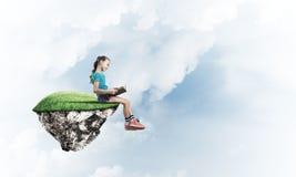 粗心大意的愉快的童年的概念与女孩阅读书的 免版税库存照片