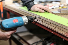 从粗纸板的聚集的家具,使用一把无绳的螺丝刀,关闭  图库摄影