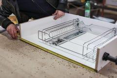 从粗纸板的聚集的家具,使用一把无绳的螺丝刀,关闭  库存照片