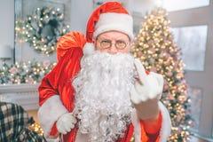 粗鲁和恼怒的男服圣诞老人项目衣裳 他在照相机显示 人拿着红色袋子单手 库存照片
